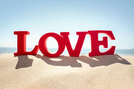 Liebeswort auf einem Sandstrandkonzept für Romance oder romantische Ferien und Feiertag