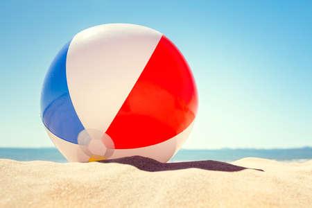 Wasserball, der im Sanddünekonzept für Kindheitssommerferien, Familienurlaub und gesunden Lebensstil stillsteht Standard-Bild