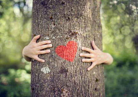 Baumumarmen, kleiner Junge, der einen Baum eine Umarmung mit rotem Herzkonzept für Liebesnatur gibt Lizenzfreie Bilder