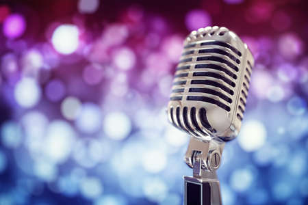Retro singing microphone with stage lighting background