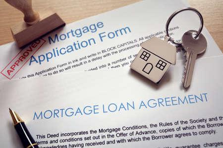 Hypothekendarlehensvertragsantrag mit Schlüssel auf Haus formte Schlüsselring Standard-Bild
