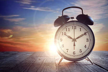 Alarm clock on wood table at sunset Lizenzfreie Bilder
