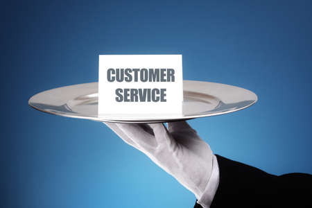 Butler or waiter holding a card reading customer service on a silver platter concept for first class or excellence
