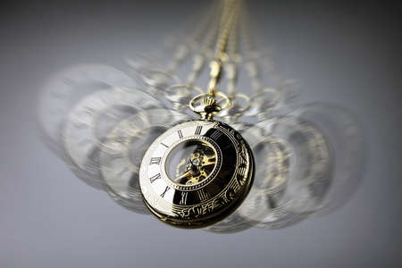 Hypnotism concept, gold pocket watch swinging used in hypnosis treatment 스톡 콘텐츠