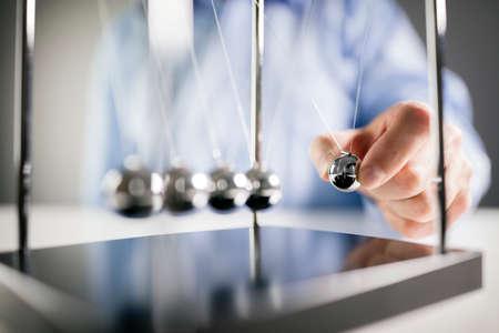 ニュートンの揺りかごビジネスマンが原因と効果のためのボールコンセプトをリリース 写真素材