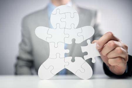 Geschäftsmann, der menschliches Teamangestelltkonzept des Puzzlespiels zusammenbaut