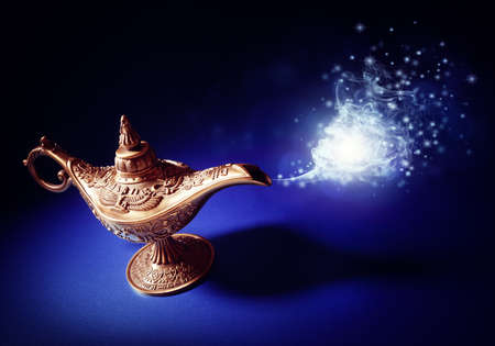 Magic lamp from the story of Aladdin with Genie appearing in blue smoke concept for wishing, luck and magic