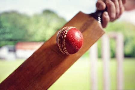 Batteur de cricket frapper une balle tirée d'en bas avec des souches sur le terrain de cricket Banque d'images