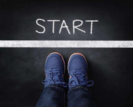 Start line child in sneakers standing next to chalk starting line on blackboard Standard-Bild