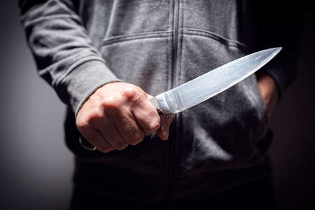 Criminal with knife weapon threatening to stab Standard-Bild