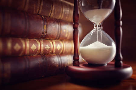 Old books and hourglass in llibrary Stock Photo