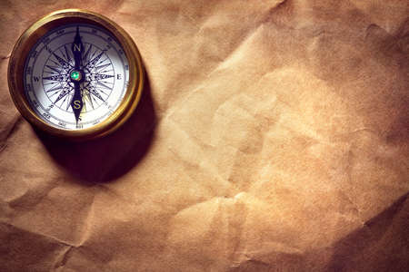 Antique golden compass on paper background with copy space Standard-Bild