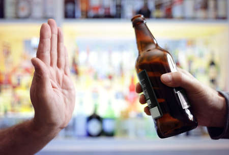 Hand rejecting alcoholic beer beverage concept for alcoholism and addiction Stock Photo