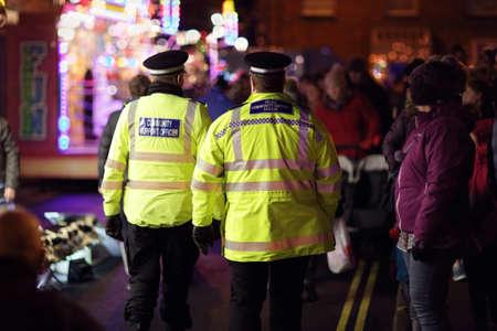 Politie in hi-zichtbaarheidsjacks die menigtecontrole controleren bij een UK gebeurtenis