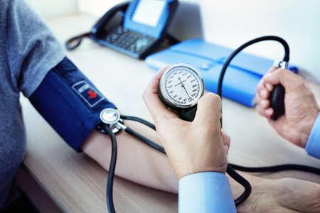 Doktor, der den Blutdruck eines Patienten überprüft Standard-Bild