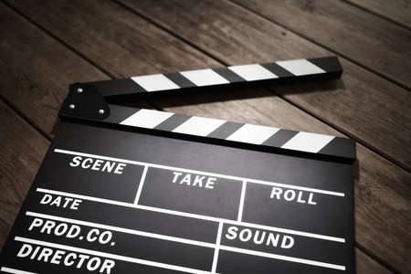 Film slate or movie clapper board on wood background Stockfoto