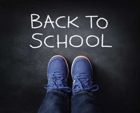 Back to school child in sneakers standing next to chalk writing on blackboard Stockfoto