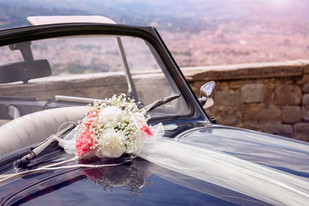 Vintage wedding car with bouquet of flowers and ribbon on bonnet Stockfoto