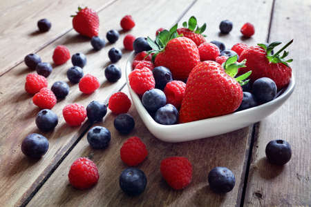 Strawberry, blueberry and raspberry fruit in a bowl on wood table antioxidant organic superfood concept for healthy eating and nutrition Stockfoto