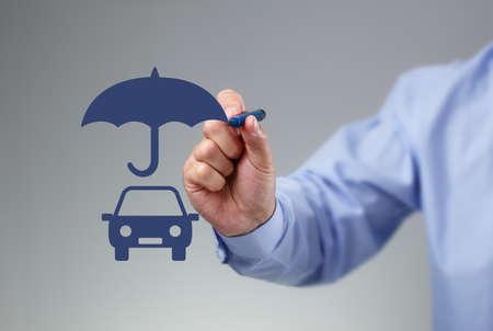Geschäftsmannhand, die einen Regenschirm über einem Familienautokonzept für Autoversicherung, Schutz, Sicherheit und Finanzen zeichnet