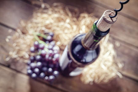 Bottle of wine, grapes, cork and corkscrew on wooden table Stockfoto