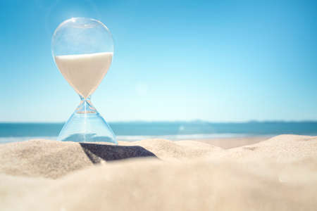 Hourglass time on a beach in the sand with blue sky and copy space 스톡 콘텐츠