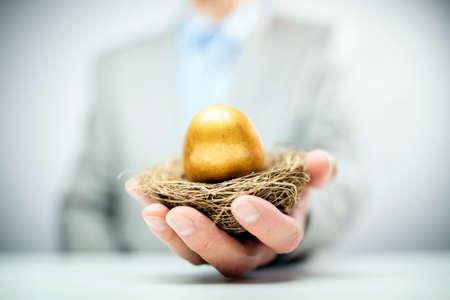 Retirement savings golden nest egg in a businessmans hand
