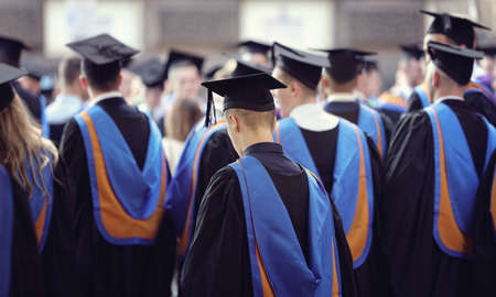 Graduates at university graduation  ceremony wearing mortarboard and gown