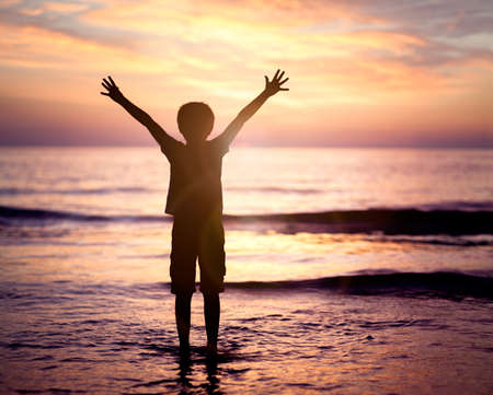 Silhouette of a boy with hands raised in the sunset over the sea concept for religion, worship, prayer and praise Banco de Imagens