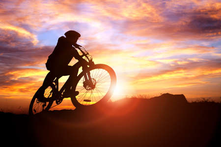 Mountain biker silhouette against the sunset concept for achievement, conquering adversity and  exercising Stockfoto