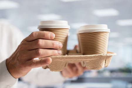 Businessman carrying coffee take out disposable cups for office meeting