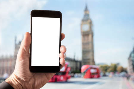 Hand holding smartphone with blank screen in London in front of Big Ben and Houses of Parliament on Westminster Bridge Stockfoto