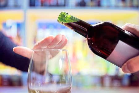 Mano de mujer rechazando más alcohol de una botella de vino en el bar