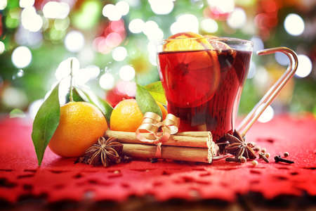 Christmas background with hot mulled wine, oranges, cinnamon sticks in front of tree Stockfoto