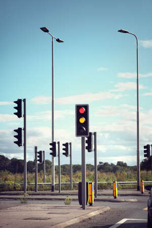 Traffic lights for cars on a road changing from red orange to green