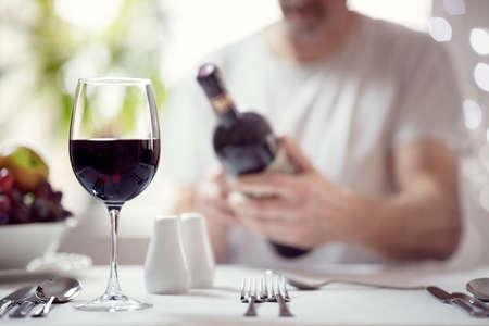 Man reading red wine bottle label in restaurant focus on glass Banque d'images