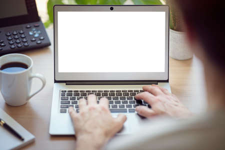 Man with laptop computer on desk working in office with blank screen Banque d'images