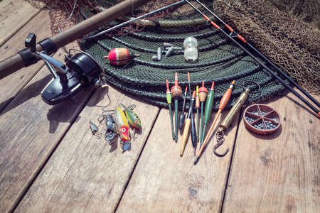 Fishing rod, reel, floats and tackle background on wooden jetty by river Banque d'images