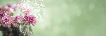 Blumenstrauß aus gealtertem rotem Rosenrand oder Banner auf Grün mit Kopierraum Standard-Bild