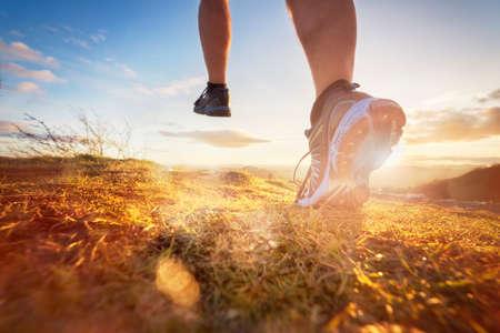 Buiten cross-country hardlopen in het ochtendzonsopgangconcept voor sporten, fitness en een gezonde levensstijl