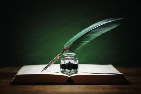 Federkiel und Tintenfass ruhen auf einem alten Buch mit grünem Hintergrundkonzept für Literatur, Schreiben, Autor und Geschichte