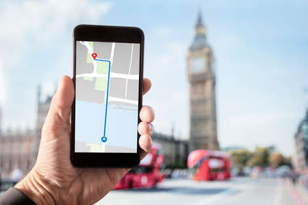 Hand holding smartphone with map on screen in London in front of Big Ben and Houses of Parliament on Westminster Bridge