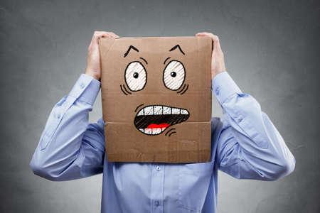 Zakenman met kartonnen doos op zijn hoofd met een geschokt en verrast uitdrukkingsexpressieconcept voor mislukking, verrassing, angst, angst of ongeloof Stockfoto