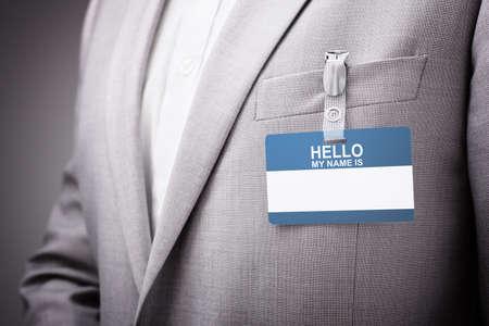 Biznesmen na wystawie lub konferencji ubrany w Hello my name is security personal card lub tag