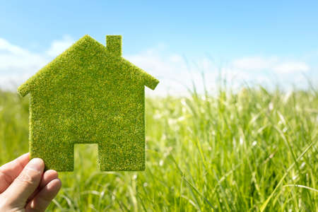 Green eco house environmental background in grass field for future residential building plot Фото со стока