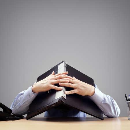 Homme d'affaires frustré et surmené enterrant sa tête sous un ordinateur portable demandant de l'aide