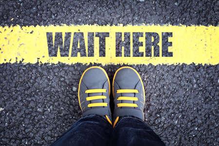 Wacht hier voeten rij achter gele wachtrij Stockfoto