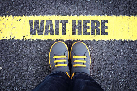Wait here feet queue behind yellow waiting line 스톡 콘텐츠 - 131760252