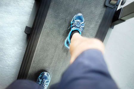 Man looking down running in a gym on a treadmill concept for exercising, fitness and healthy lifestyle
