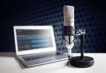 Podcast microphone and laptop computer on desk in recording studio Banque d'images